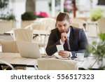 Small photo of Confident serious business man in formal wear sitting on terrace of urban cafe and using phone while enjoying morning coffee