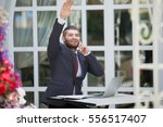 Small photo of Handsome smiling businessman with laptop talking on phone and calling waiter while sitting outdoors in urban cafe during coffee break