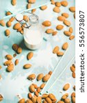 Small photo of Dairy alternative milk. Almond milk in bottle and fresh nuts over blue background, selective focus, copy space. Clean eting, dairy-free, vegan, allergy-friendly, vegetarian, raw, healthy food concept