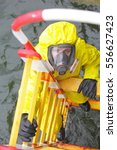 Small photo of overhead view of specialist in protective suit and mask on ladder above water