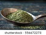 dill weed in an antique spoon | Shutterstock . vector #556672273