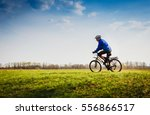 young man cycling on a rural... | Shutterstock . vector #556866517