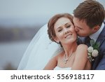 bride and groom embracing on a... | Shutterstock . vector #556918117
