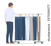 man near rack with pants.... | Shutterstock .eps vector #557039377