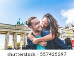 Stock photo happy couple having fun in berlin mixed race couple a caucasian man giving a piggyback ride to 557425297