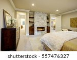 Small photo of Beige and brown master bedroom boasts queen bed facing gorgeous stone fireplace framed by shelves. Northwest, USA