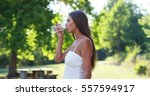 the young woman drinks a glass... | Shutterstock . vector #557594917