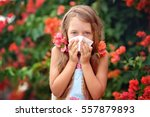 Small photo of Allergy. Little girl is blowing her nose near spring tree in bloom. Closeup portrait