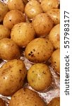 Small photo of Organic white potatoes in an oven tray on tin aluminium foil