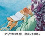 Small photo of Young muslim woman praying in mosque with Quran - the holy book of Islam