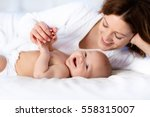 mother and child on a white bed.... | Shutterstock . vector #558315007