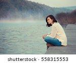 girl  sitting by lake   Shutterstock . vector #558315553