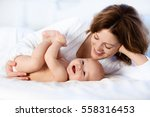 mother and child on a white bed.... | Shutterstock . vector #558316453