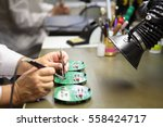 Small photo of Electronics Manufacturing Services, Manual Assembly Of Circuit Board Soldering, close-up of the hand women hold tool.