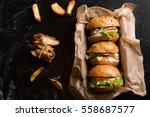 Three Burgers On A Dark Wooden...