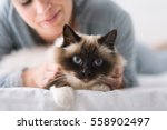 Stock photo smiling woman lying on the bed and cuddling her soft beautiful cat pets and lifestyle concept 558902497