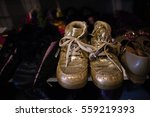 Small photo of Golden glittery shoes that were worn by a child at some point.