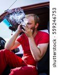 Small photo of tired stern man in a red t-shirt smoking a cigarette sitting in a jeep with the door open, adventure require overcoming obstacles, blonde speaks by phone serious business problem solution, smoke run