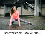 Small photo of Sporty young woman stretching long adductor for warming up before urban fitness workout or running training. Caucasian female athlete doing leg stretch exercise outside on rainy winter day.