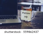 Small photo of Sticky note with FOLLOW US wording on glass of tea with laptop on wooden table. Motivation and positive wishes concept