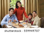 Small photo of woman stands over dinner table with smiling family