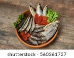 Small photo of Salty stockfish on wooden table. Rainbow smelt, Common bream, Vobla, Shemay, Macrourus caviar and lettuce leaves.