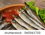 Small photo of Salty stockfish on wooden table. Rainbow smelt, Vobla, Macrourus caviar and lettuce leaves.