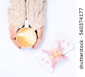 Small photo of Female hands in beige knit holding cup of cappuccino. Gift alike dessert with heart shape sprinkles. Flat lay. Valentines concept. Square