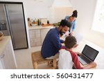Small photo of Parents helping kids with homework in kitchen, elevated view