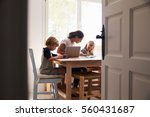 Small photo of Mum and two kids working in kitchen, close up from doorway