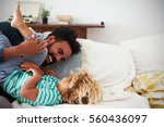 father and son playing game on... | Shutterstock . vector #560436097