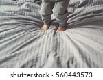 a child jumping on the bed.... | Shutterstock . vector #560443573