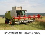 Combine In Oilseed Rape Field...