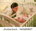 Dad With A Baby In A Crib