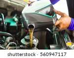 Small photo of Car mechanic replacing and pouring fresh oil into engine at maintenance repair service station