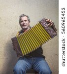 Small photo of man playing accordion in the street