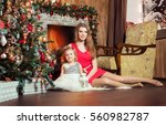 cute blond mom in red dress... | Shutterstock . vector #560982787