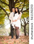 Small photo of Couple maternity photo in fall under the tree with leaves on the ground