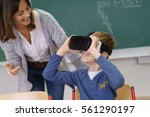 smiling teacher watching a... | Shutterstock . vector #561290197