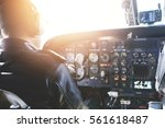 Small photo of Adult airplane pilot wearing headset and outfit performing his job, sitting inside aircraft cockpit at steering control with modern dashboard. Bright sunshine penetrating into cabin through glass