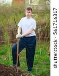 Small photo of Agronomist handsome strong man with shovel on the background of flower beds