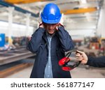 worker protecting his ears from ... | Shutterstock . vector #561877147