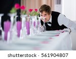 handsome waiter looking at... | Shutterstock . vector #561904807