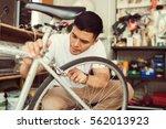 man bicycle mechanic repairing... | Shutterstock . vector #562013923