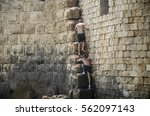 Small photo of Two teenage boys climbing up a steep staircase on a wall in Akko, Israel. Brave adolescent teens taking a risk by climbing a wall. Tough guys working out by climbing and overcoming challenging wall.