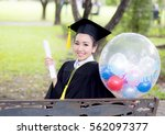 Small photo of Portrait of happy young female graduates in academic dress and square academic cap holding word quotes of CONGRATS GRAD on balloon after convocation ceremony.