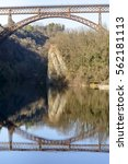 Small photo of arch of old iron bridge reflected by river Adda waters, shot in bright light at Paderno, Lomabrdy, Italy
