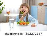 small girl eating vegetables in ... | Shutterstock . vector #562272967