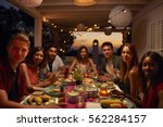 friends at a dinner party on a... | Shutterstock . vector #562284157
