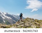 hiker going along green hills... | Shutterstock . vector #562401763